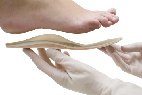 Image of an orthotic insoles being fitted to a patient